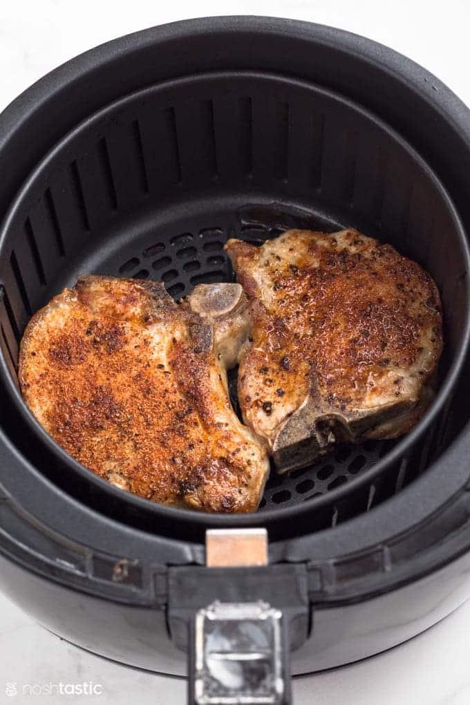Pork chops inside the air fryer basket for an easy air fryer pork chop recipe