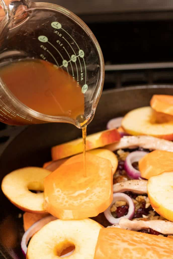 Pouring apple juice mixture over top of the stuffed pork chops