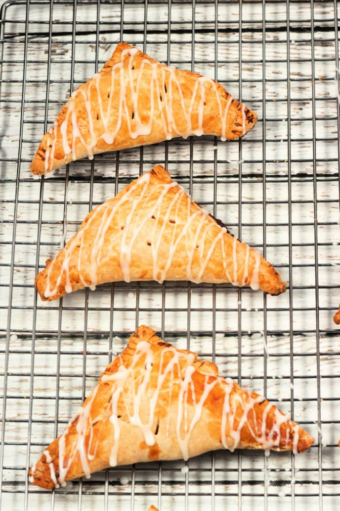 Apple turnovers fresh out of the oven, on a cooling rack and drizzled with icing.