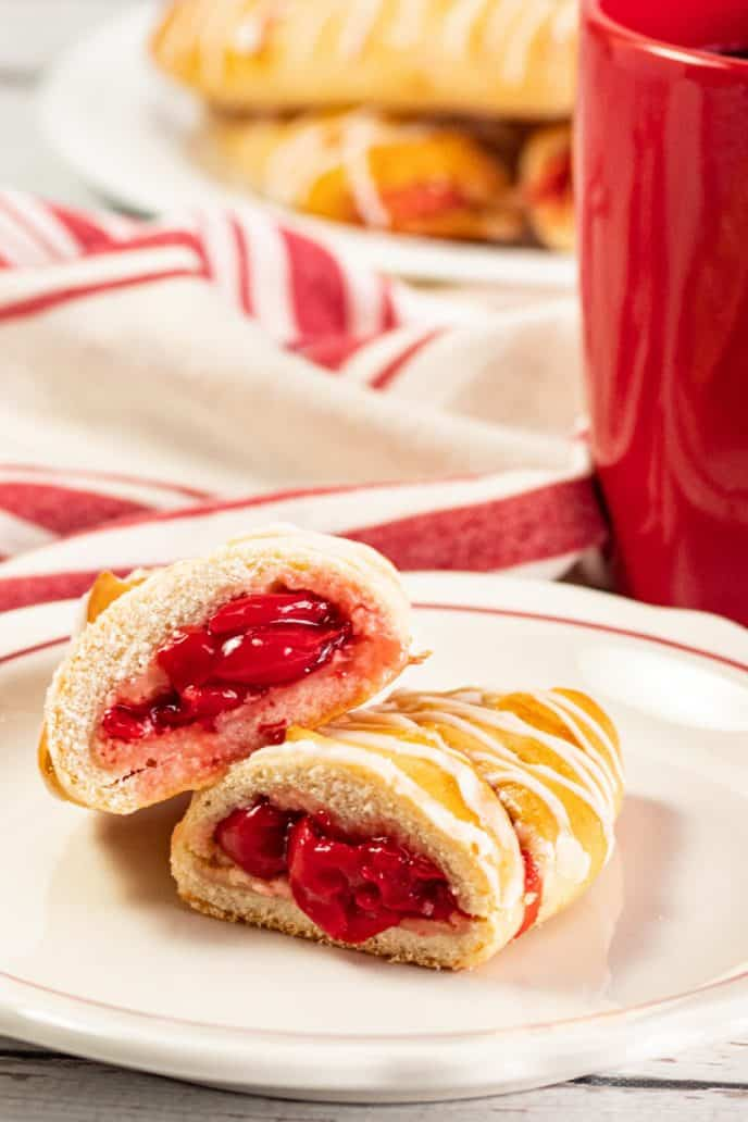Cherry Danish pastry on a plate with a dish full of pastries in the background
