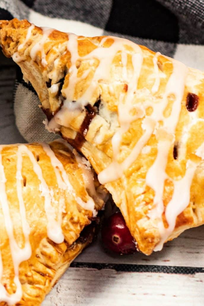 Apple turnovers with cranberry apple filling, baked golden brown and drizzled with icing.