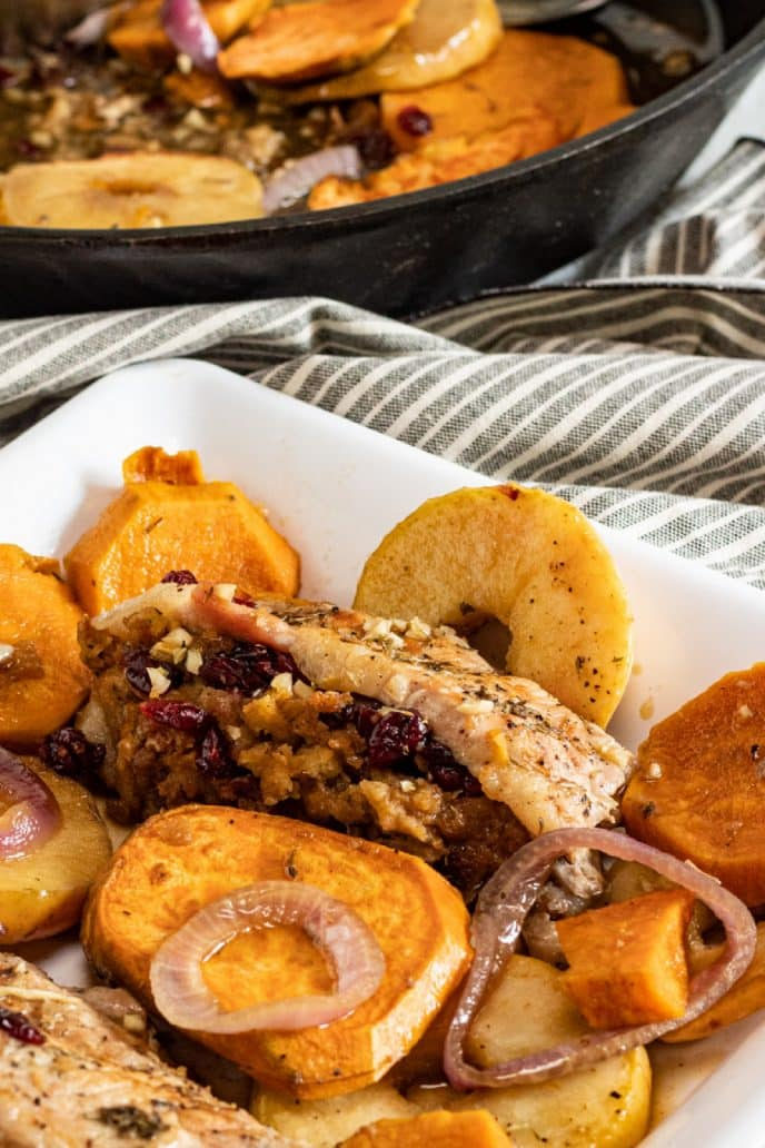 Stuffed Pork Chops Recipe completed with cherry stuffing, apples, sweet potatoes on a plate with cooking skillet in background