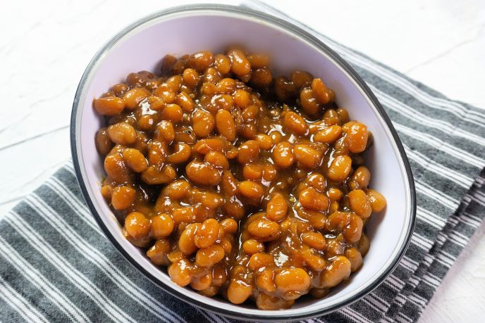 An oval bowl filled with instant pot homemade baked beans from scratch.