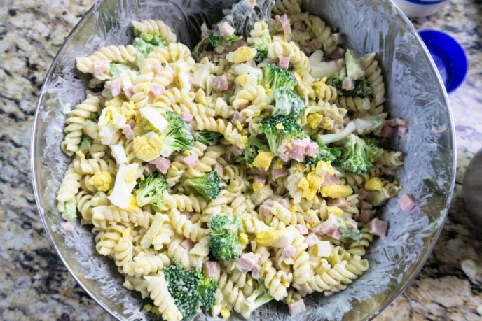 Pasta salad recipe ingredients all mixed together in a bowl.