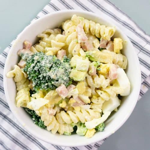 Pasta salad recipe with ham, broccoli, avocado, and dressing.