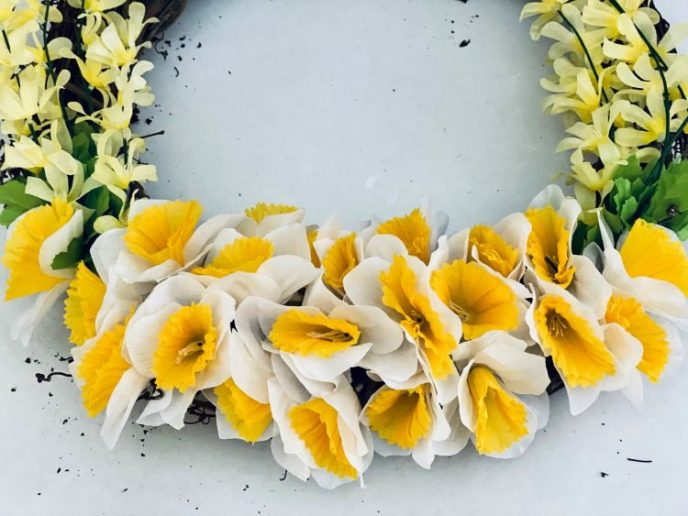 Attaching daffodils to the grapevine wreath.