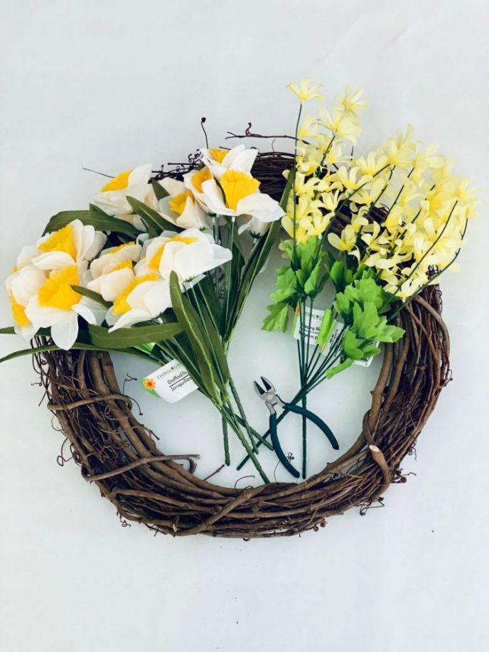 Supplies to make a grape vine wreath with daffodil flowers.