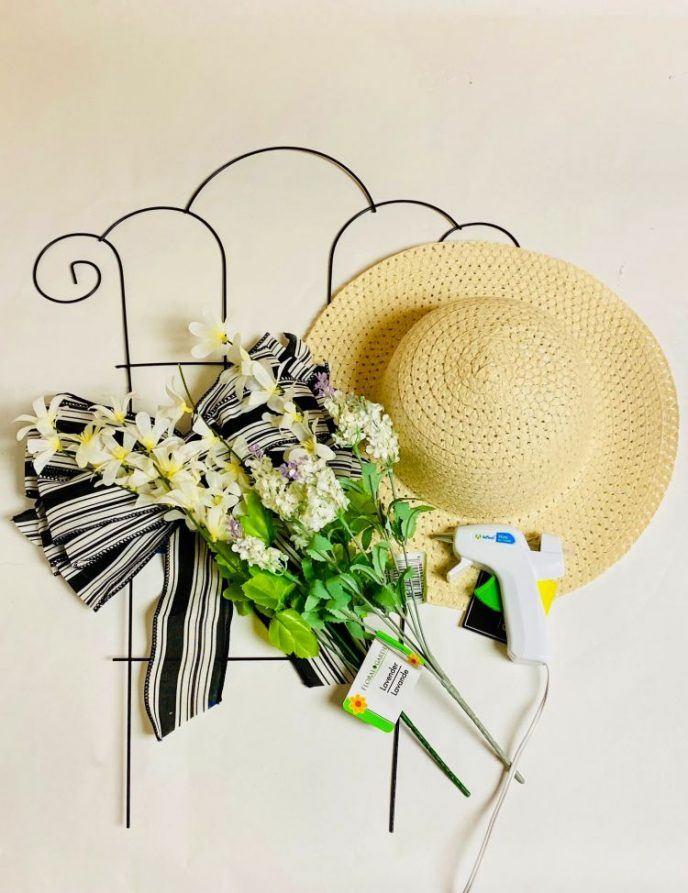 Materials to make a sun hat craft, sun hat, bow, flowers, and trellis.
