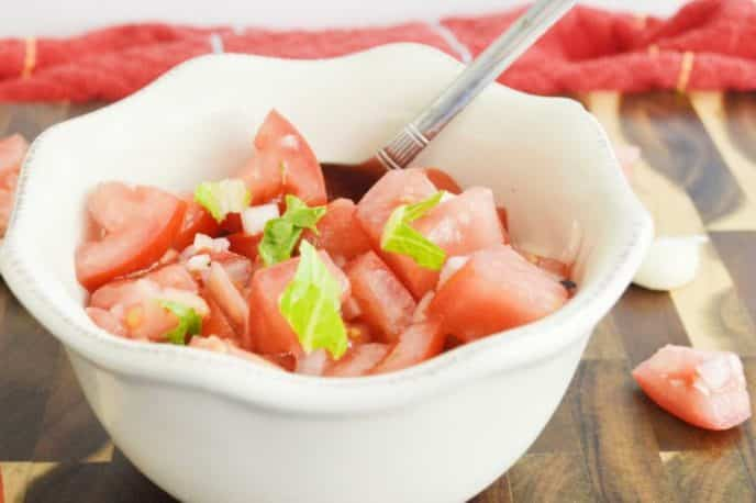 Tomato salad recipe with basil and onion, perfect side dish served in a white flower patterned bowl