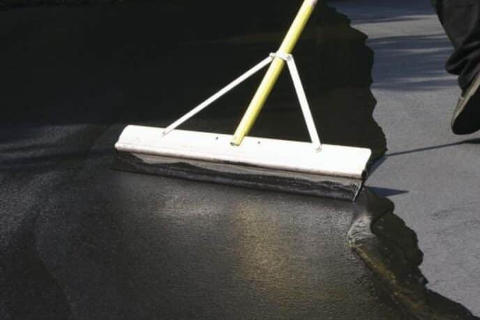 Sealing an asphalt driveway with a squeegee