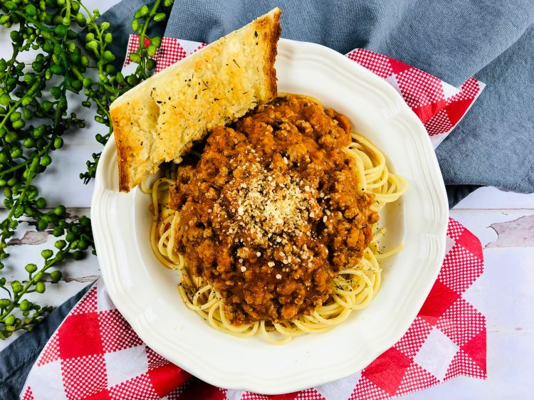 Homemade spaghetti sauce in a while bowl served over spaghetti pasta with a side of garlic bread.