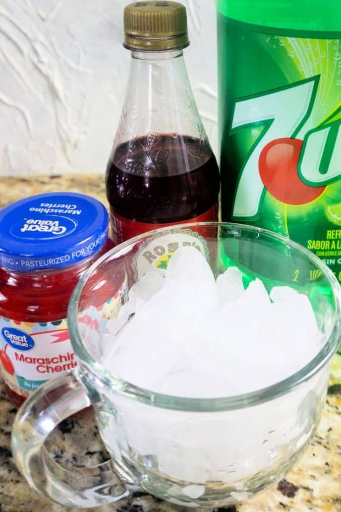 Shirley temple ingredients on the counter such as soda, grenadine, cherries, and ice.