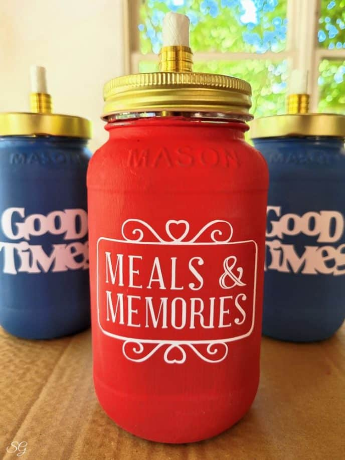 Tabletop mason jar tiki torches, a red torch and two blue mason jars with white vinyl designs that say Good Times and Meals & Memories on them.