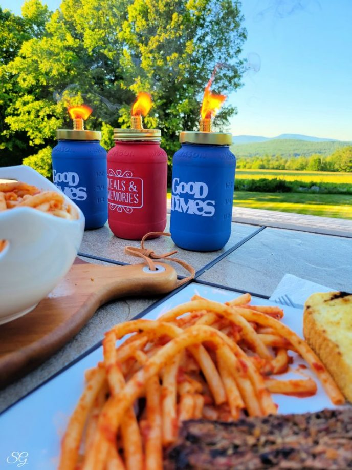 DIY Tiki Torches on a patio table with mountains and trees in the background and pasta on a plate in the foreground