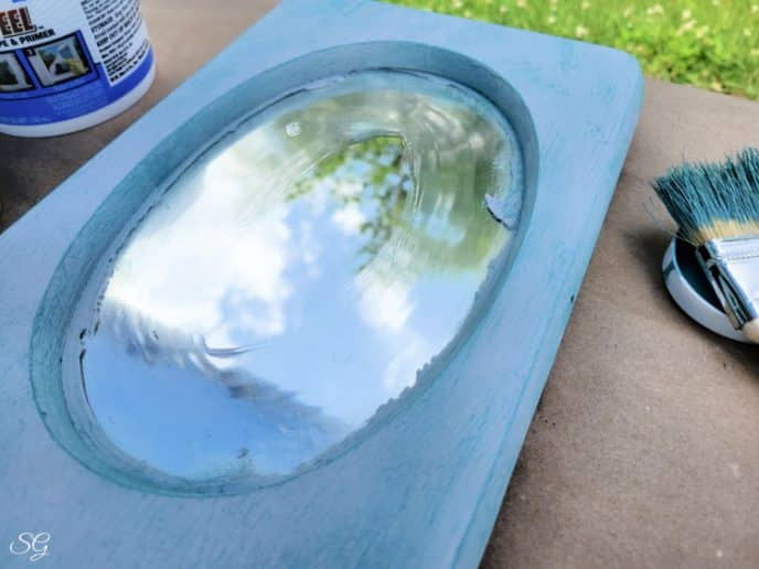 Dry brush painting turquoise over gray on the mirror frame around the oval mirror