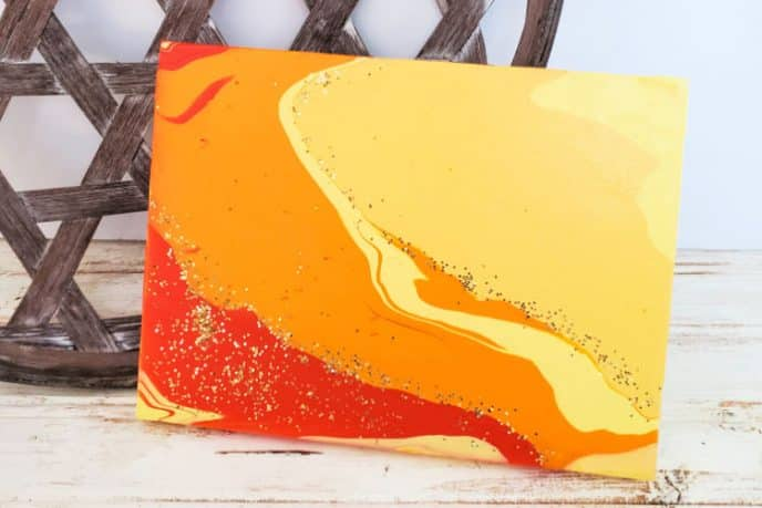 Acrylic paint pour art with light brown, orange, and red colors swirled across the canvas