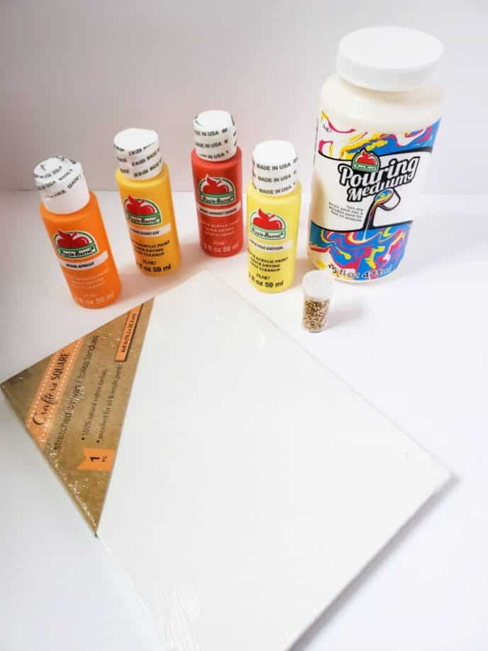 Materials for acrylic paint pour such as paint, canvas, pouring medium and tools needed.