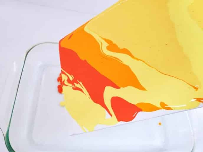 Tilting the canvas to flow the paint over the entire surface and edges