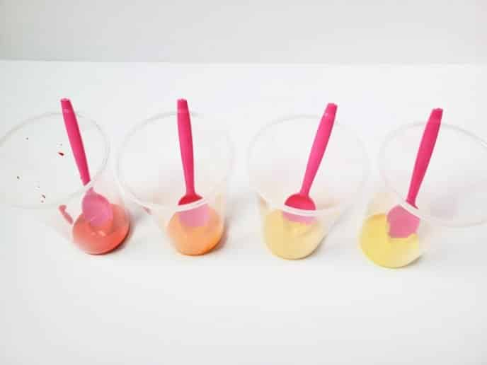 Acrylic paint in clear plastic cups with pink plastic spoons